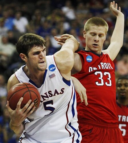 Kansas center Jeff Withey (5) is fouled by Detroit forward Evan Bruinsma (33) during the second half of an NCAA college basketball tournament game at CenturyLink Center in Omaha, Neb., Friday, March 16, 2012. Kansas defeated Detroit 65-50. (AP Photo/Orlin Wagner)